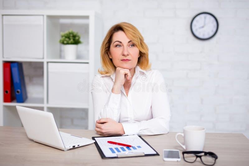 坐在办公室的哀伤的成熟的商业妇女 库存图片
