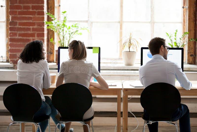 坐在分享的办公室后方后面见解的妇女和人 免版税库存照片