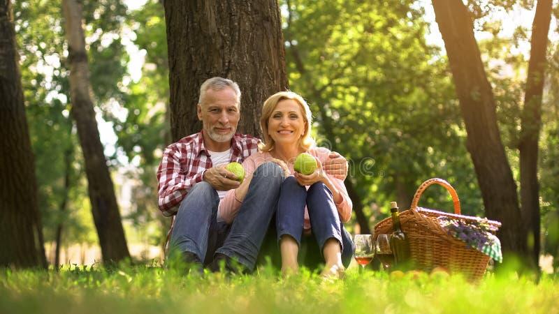 坐在公园和吃绿色苹果,野餐,家庭周末的资深夫妇 库存图片