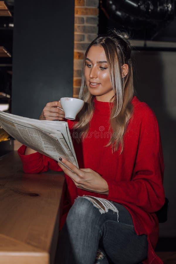 坐在咖啡馆和读报纸的年轻女人 图库摄影