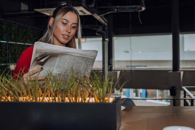 坐在咖啡馆和读报纸的美丽的年轻女人 免版税库存图片