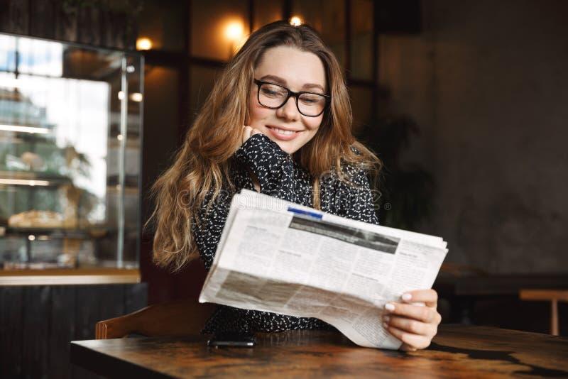 坐在咖啡馆的美丽的年轻女人户内读报纸 免版税库存图片