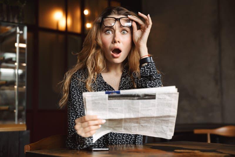 坐在咖啡馆的美丽的震惊激动的年轻女人户内读报纸 免版税库存照片