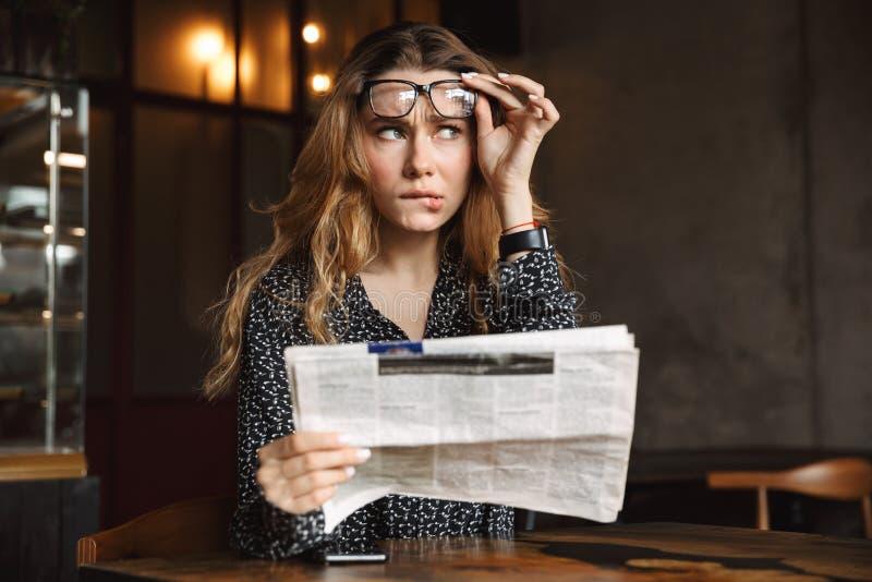 坐在咖啡馆的迷茫的年轻女人户内读报纸 图库摄影