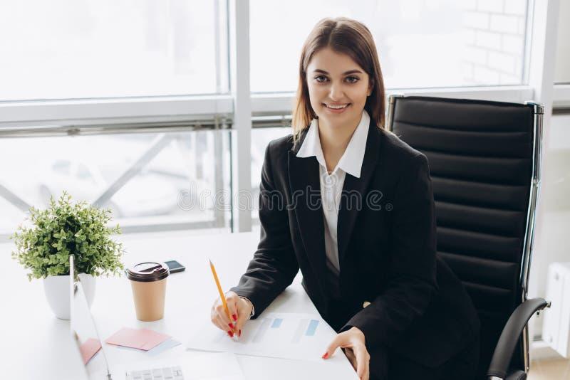 坐在桌上在办公室和看照相机的一名快乐的女实业家的画象 库存图片