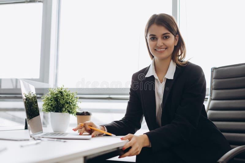 坐在桌上在办公室和看照相机的一名快乐的女实业家的画象 图库摄影