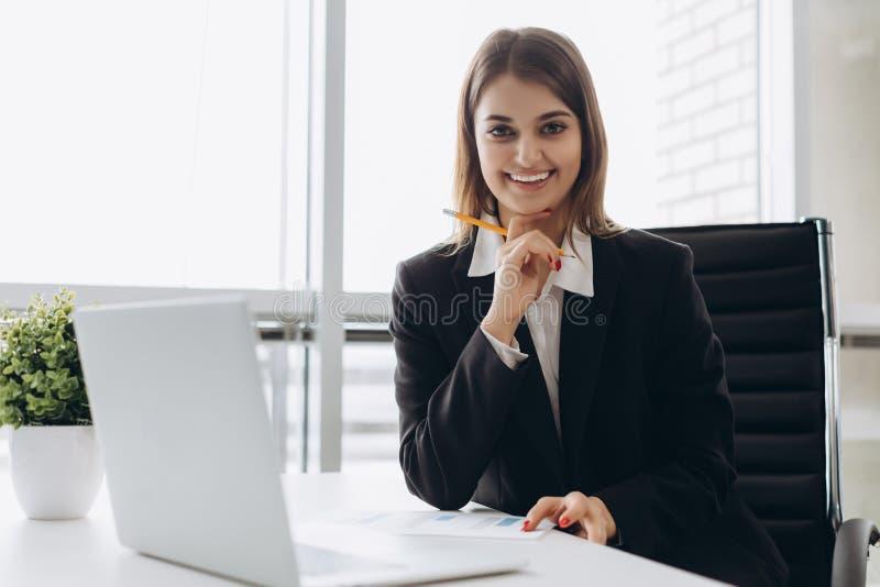 坐在桌上在办公室和看照相机的一名快乐的女实业家的画象 库存照片