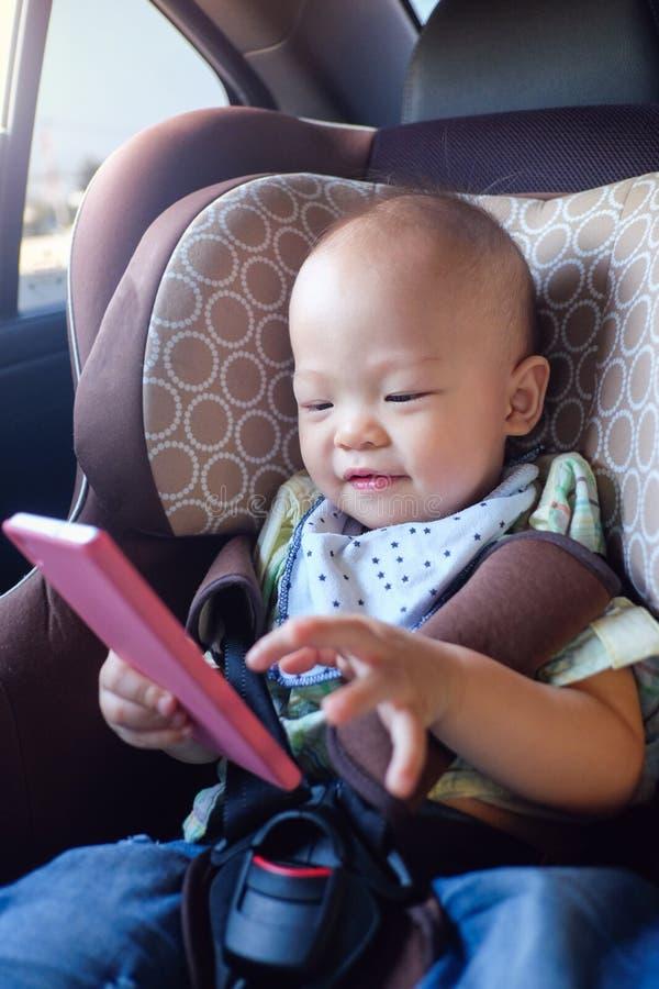 坐在汽车座位和观看从智能手机的亚裔小孩男婴录影 免版税图库摄影