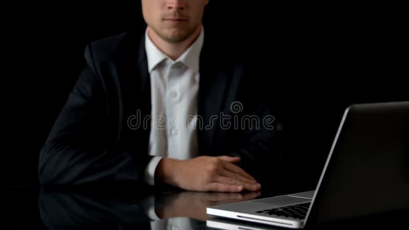 坐在膝上型计算机前面的严肃的商人,运转直到夜间 库存照片