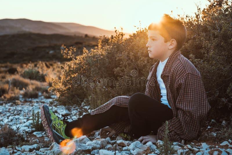 坐在领域的一个小白肤金发的男孩的画象 日落的英俊的小男孩 免版税库存照片