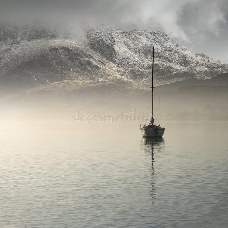 坐直在与隐约地出现在背景中的山的镇静湖水中的航行游艇的惊人的风景图象在秋天秋天期间 免版税库存照片