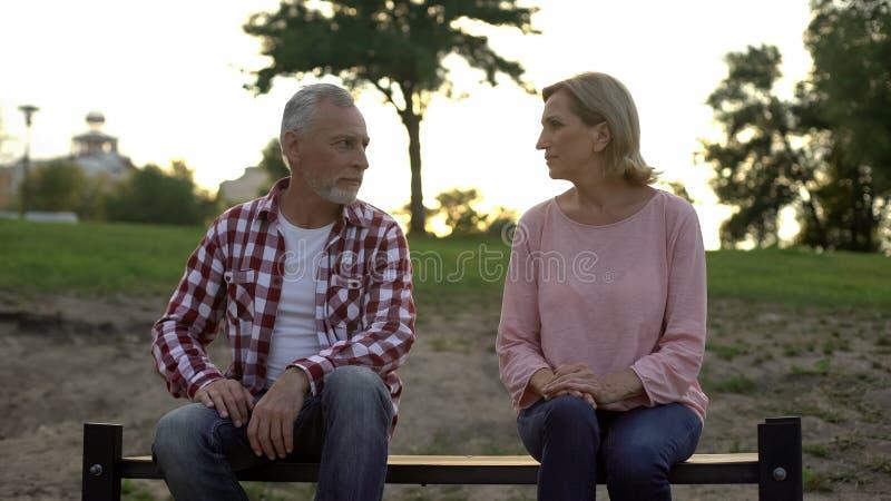坐长凳和看彼此,关系的被触犯的资深夫妇 免版税库存照片