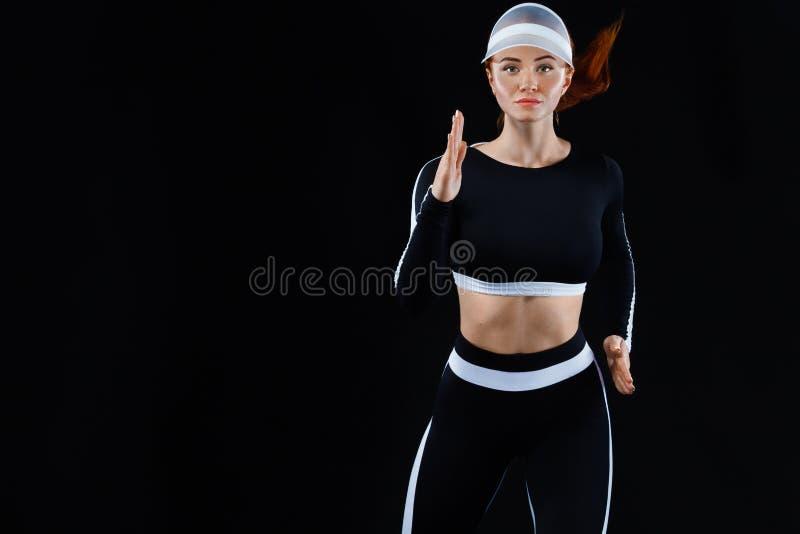 坚强的运动妇女短跑选手,跑在佩带在运动服的黑背景 健身和体育刺激 运行 库存图片