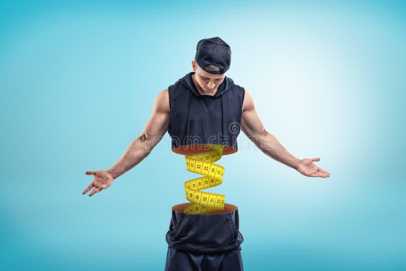 坚强的肌肉年轻人用在蓝色背景的黄色测量的磁带里面切成了两半 库存例证