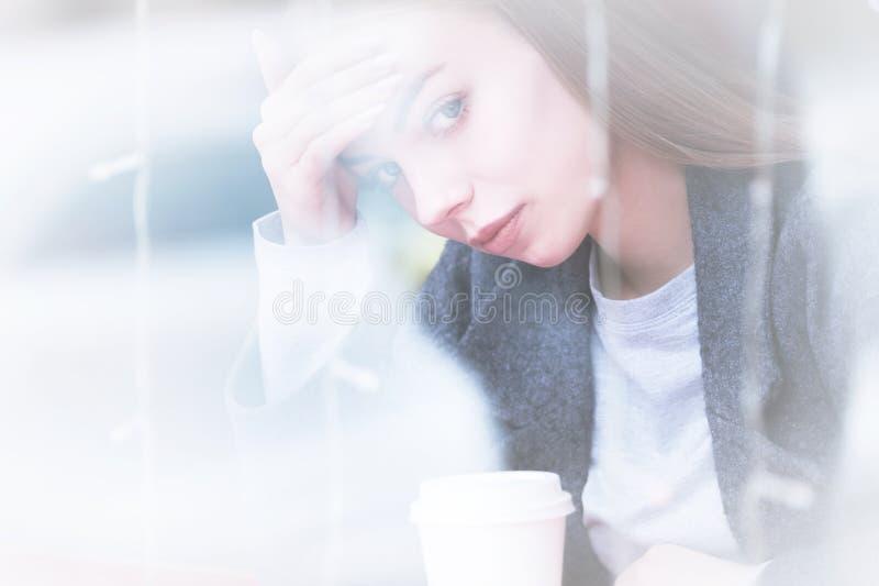 坚持她的头的一位可爱的年轻女性新闻工作者的画象担心或在一个咖啡馆的头疼在a后 图库摄影