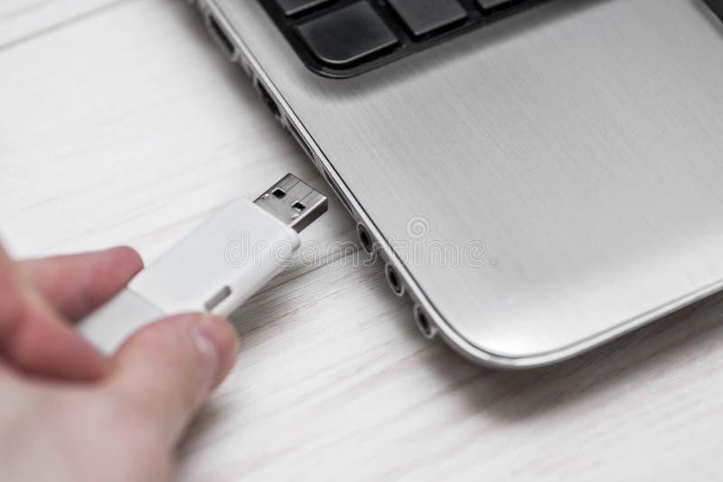 塞住可移动的闪光磁盘记忆入膝上型计算机USB槽孔 插入USB一刹那驱动的人手入在木白色的手提电脑 免版税库存图片