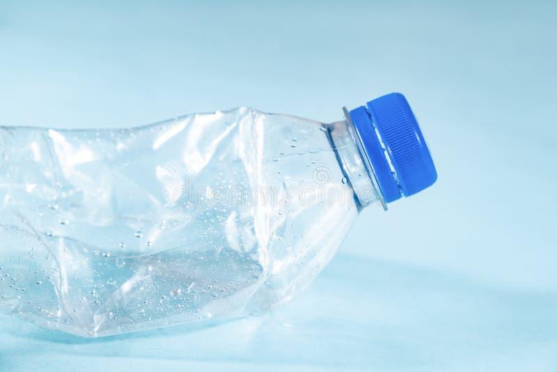 塑料废概念:被放弃的被弄皱的水瓶在蓝色背景,详细的看法中 库存照片