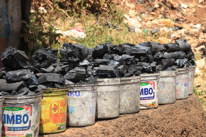 塑料桶煤炭在非洲的最贫穷的地区的街道上被卖 免版税图库摄影