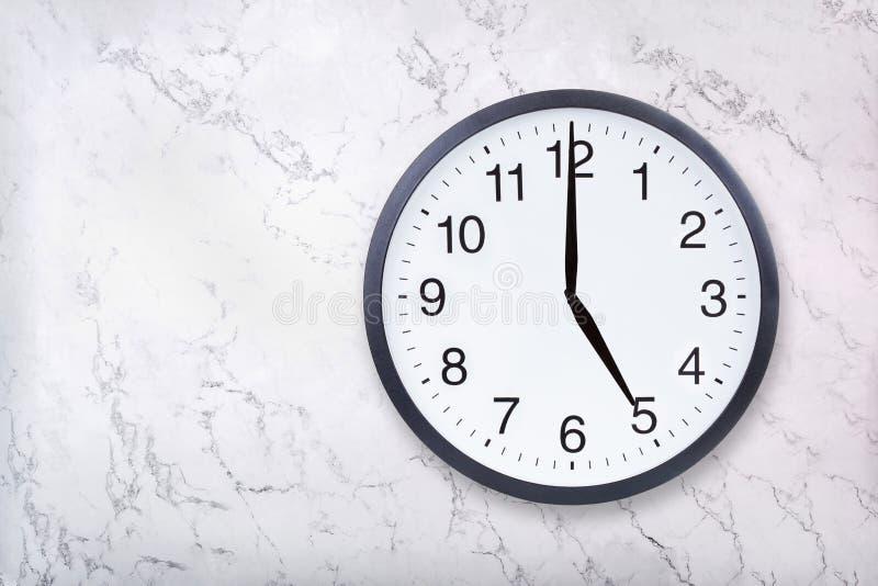 壁钟在白色大理石纹理的展示5点 办公室时钟展示下午5点或早晨5点 免版税库存照片