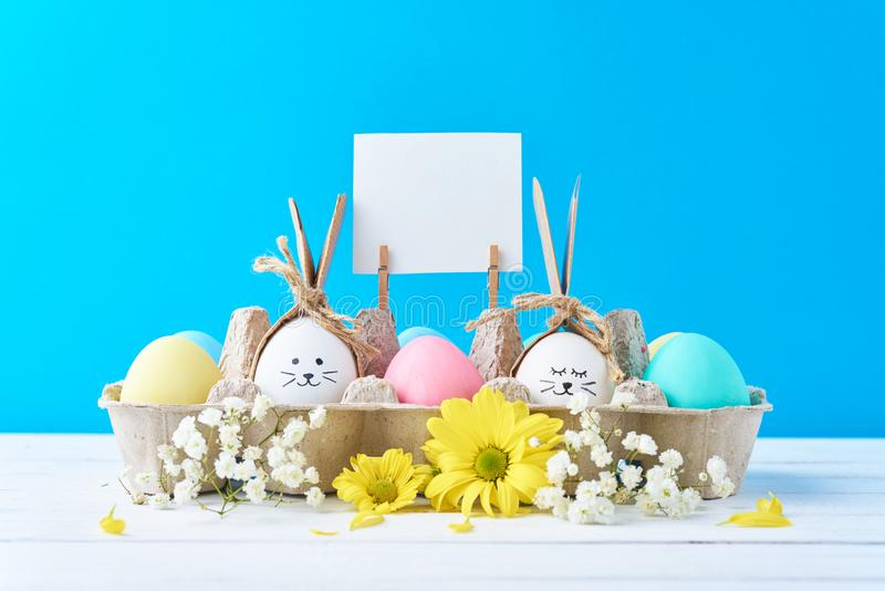 复活节上色了在载纸盘的鸡蛋有在蓝色背景的decorationd的 免版税库存照片