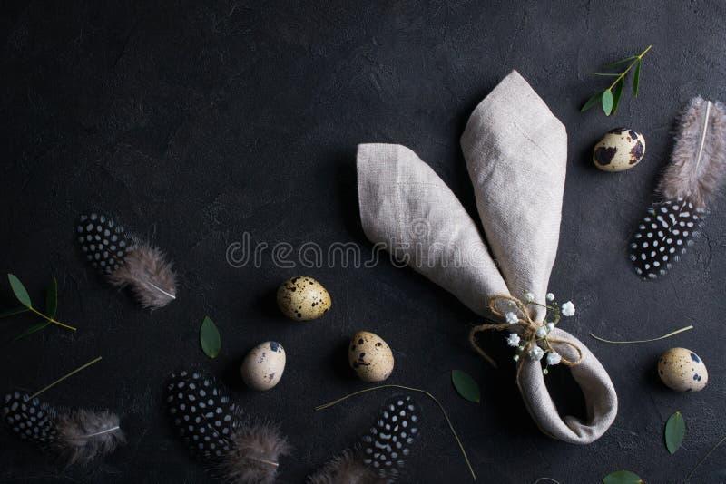 复活节假日背景用鸡蛋 鹌鹑蛋、羽毛和兔宝宝耳朵亚麻布餐巾顶视图在黑暗的生锈的背景 Copysp 免版税库存照片