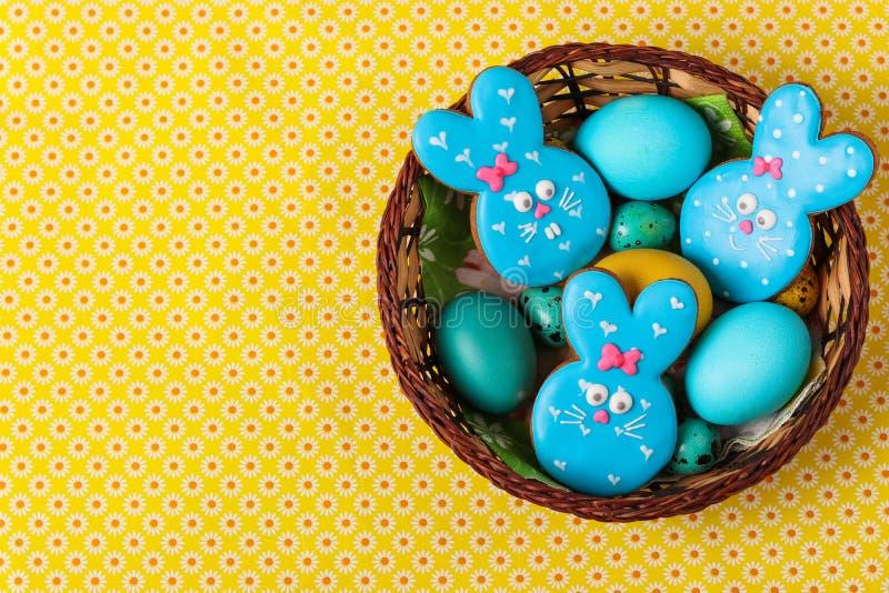 复活节姜饼兔子、黄色和蓝色鸡和鹌鹑蛋在一个柳条筐,顶视图 图库摄影