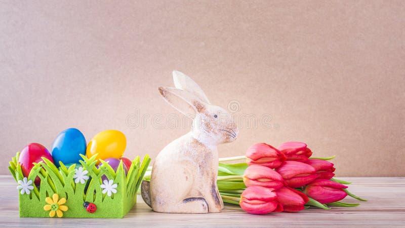 复活节巢用五颜六色的复活节彩蛋、复活节兔子和红色郁金香 免版税库存图片