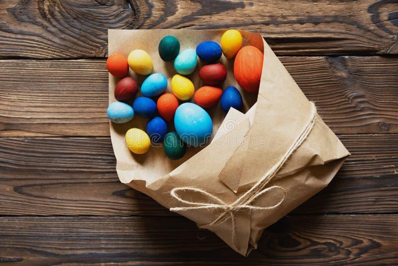 复活节彩蛋在一个纸袋被包装作为在木背景的一件礼物 库存图片