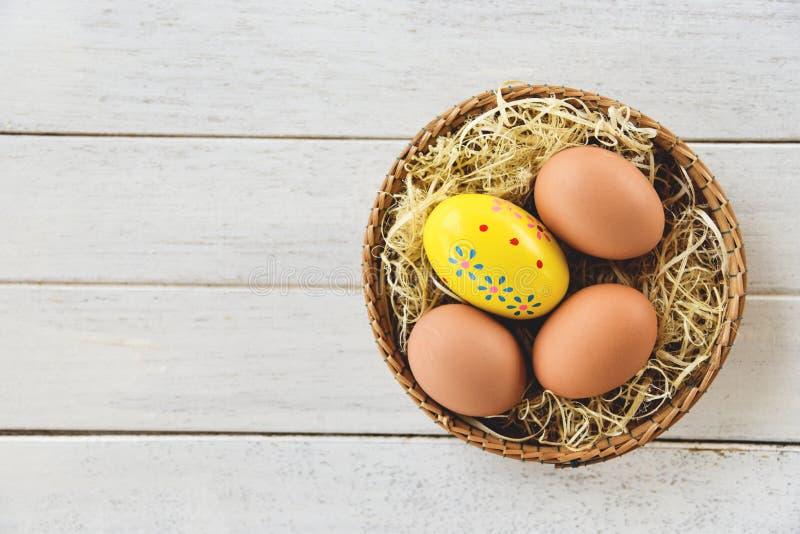 复活节彩蛋和鸡蛋篮子巢装饰在白色木背景顶视图 免版税库存照片