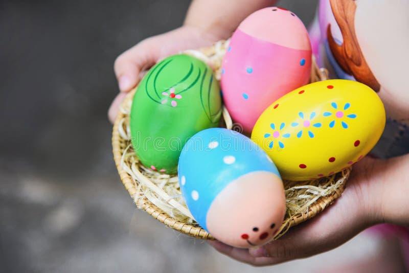 复活节彩蛋狩猎五颜六色在篮子在手边在巢绘的女孩鸡蛋 库存照片
