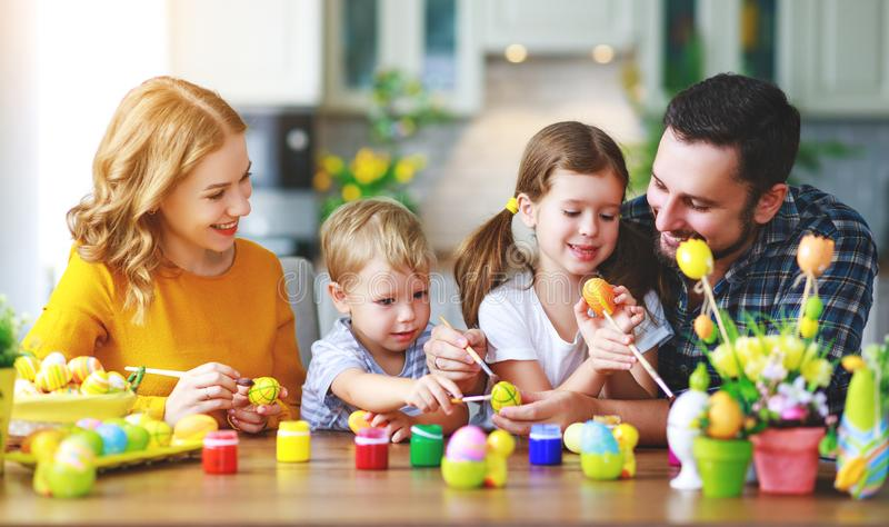 复活节快乐!家庭母亲、父亲和孩子为假日绘鸡蛋 免版税库存照片