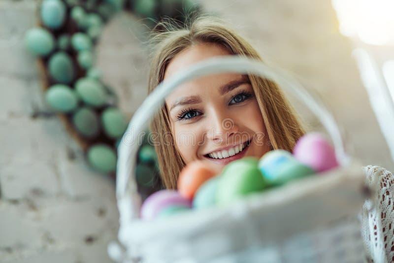 复活节快乐!有复活节彩蛋篮子的美丽的年轻女人  免版税库存图片