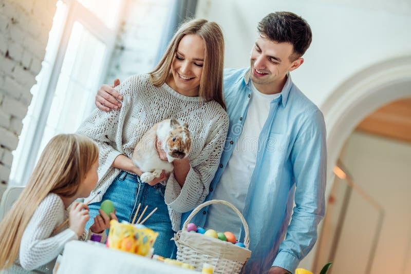 复活节准备 有她的母亲冲程的小女儿一只家庭装饰兔子 免版税库存图片