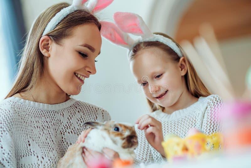 复活节准备 有她的母亲冲程的小女儿一只家庭装饰兔子 免版税图库摄影