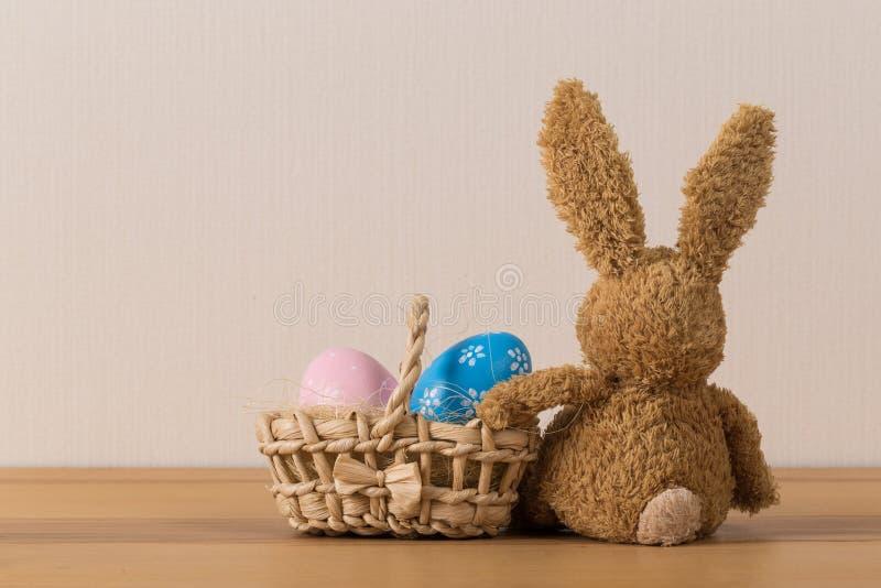 复活节兔子兔子用在木背景的被绘的鸡蛋 免版税库存图片