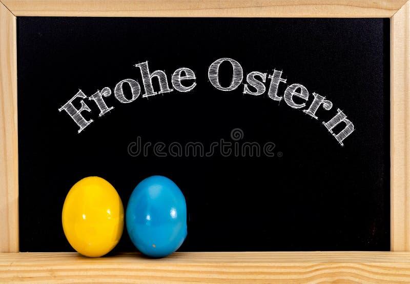 复活节框架用被绘的鸡蛋和黑板 在白色白垩的复活节快乐 复活节快乐用德语: 免版税库存照片