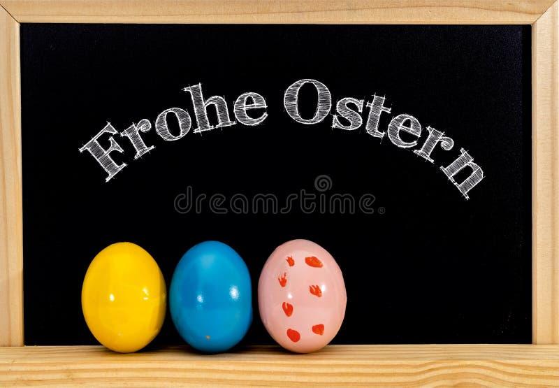 复活节框架用被绘的鸡蛋和黑板 在白色白垩的复活节快乐 复活节快乐用德语: 免版税库存图片