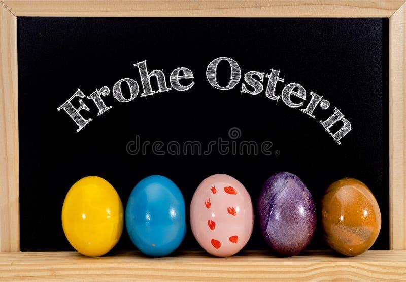 复活节框架用被绘的鸡蛋和黑板 在白色白垩的复活节快乐 复活节快乐用德语: 库存照片