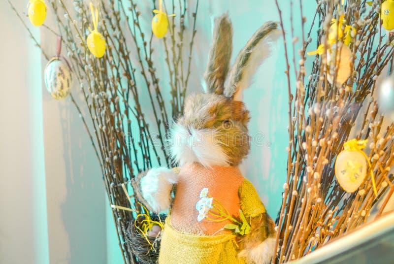 复活节构成用垂悬在蓝色背景的猫杨柳花束的玩具兔子和鸡蛋 库存照片