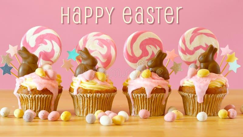 复活节糖果土地与巧克力兔宝宝和文本问候的滴水杯形蛋糕 库存图片
