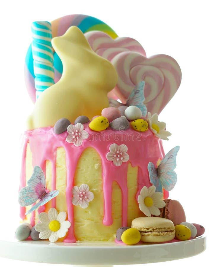 复活节糖果土地用棒棒糖和白色兔宝宝装饰的滴水蛋糕 库存照片