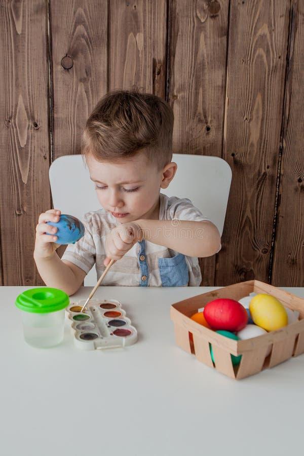 复活节的小男孩绘画五颜六色的鸡蛋在木背景 图库摄影