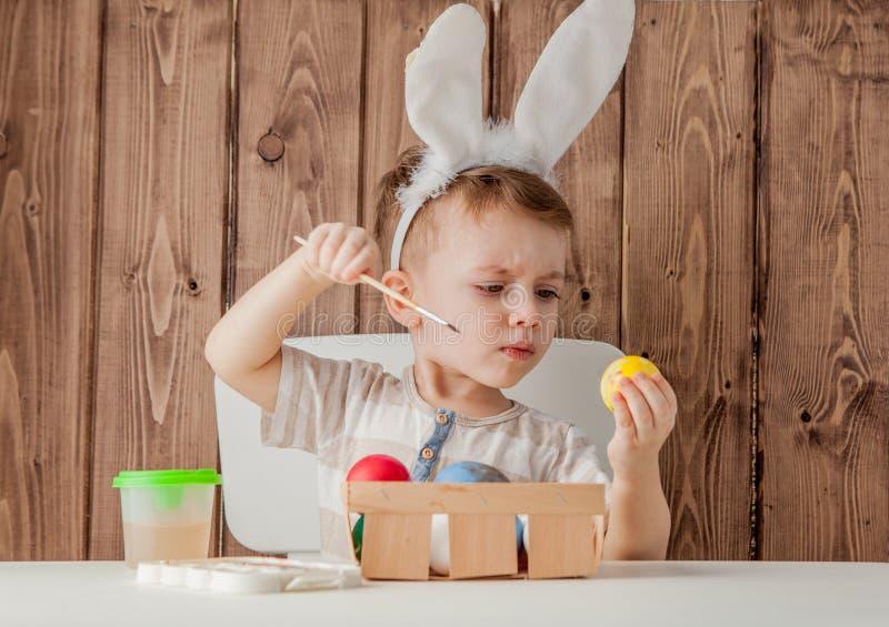 复活节的小男孩绘画五颜六色的鸡蛋在木背景 库存照片