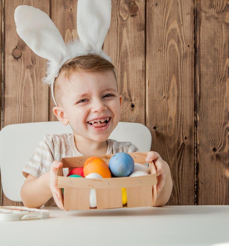 复活节的小男孩绘画五颜六色的鸡蛋在木背景 免版税库存照片