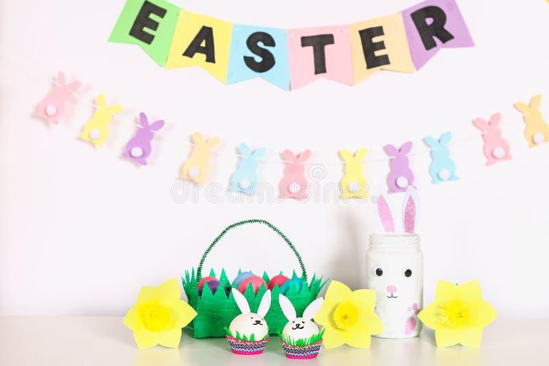 复活节的Diy装饰 纸诗歌选,花瓶兔宝宝,黄水仙,蛋兔宝宝,篮子用被绘的鸡蛋 免版税库存图片