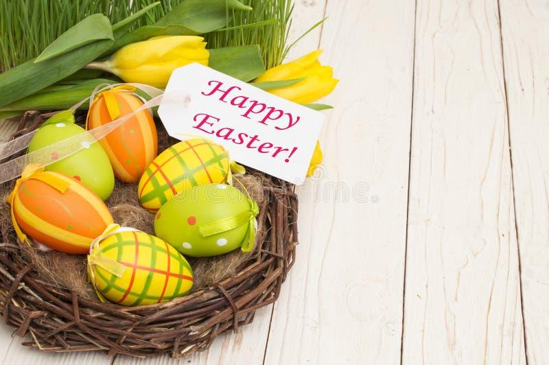 复活节装饰用鸡蛋和郁金香与词复活节快乐在木背景 库存图片