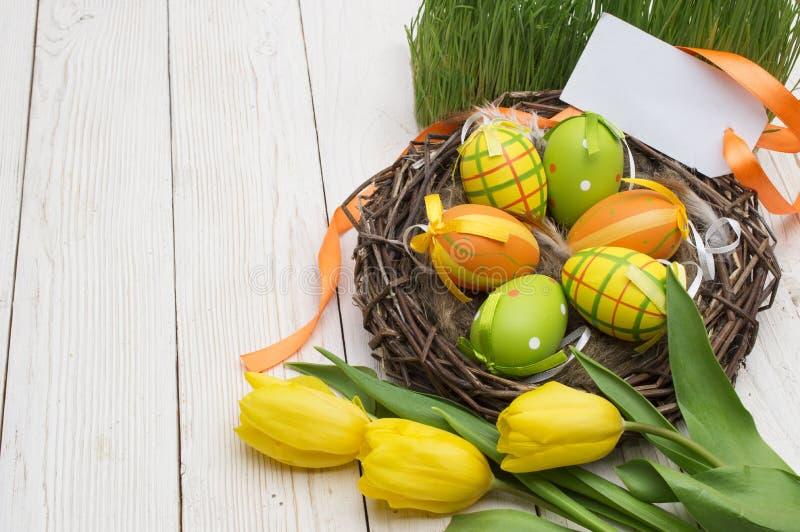 复活节装饰用鸡蛋和郁金香在木背景 库存图片
