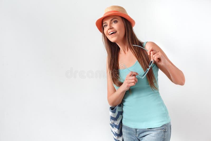 夏天心情 妇女在帽子在与拿着太阳镜的海滩袋子的白色隔绝的身分演播室看今后激发 库存图片