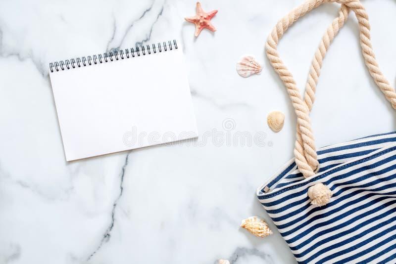 夏天在大理石背景的旅行构成 有镶边海滩袋子、贝壳和空白的笔记薄的妇女的书桌 生活方式  库存图片