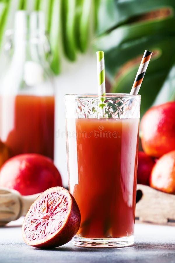 夏天汁液或非酒精刷新的健康鸡尾酒或者饮料从新近地被紧压的红色西西里人的桔子,明亮的轻的桌 图库摄影